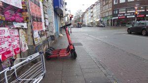 Vier E-Roller wurden von Juicern quer auf dem Gehweg aufgestellt. Davor ein Wäscheständer.
