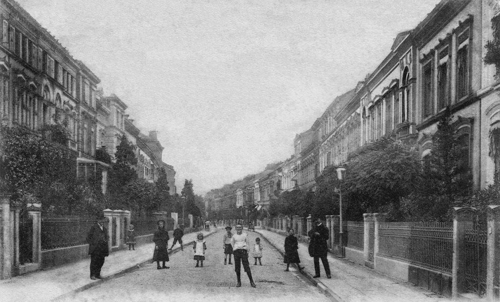 Bild zeigt eine Wohnstraße ohne Autos und mit einer Gruppe von Menschen, die verteilt auf Fahrbahn und Bürgersteigen stehen