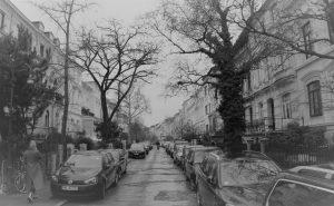 Die selbes Straße wie auf dem Bild darüber, nur heute, Januar 2021, mit beidseitig zugeparkten Gehwegen und einer Frau, am Bildrand auf dem Gehweg läuft und einem Fahrradfahrer in der Ferne.