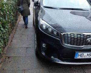 Bild zeigt einen Gehweg mit einer Efeuhecke und einer Passantin, die sich an einem, den Gehweg bis auf ca 70 cm zuparkenden SUV durchzwängt.