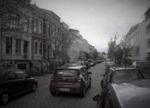 Bremer Wohnstraße mit parkenden Autos. Auto vom Pflegedienst sucht Parkmöglichkeit.