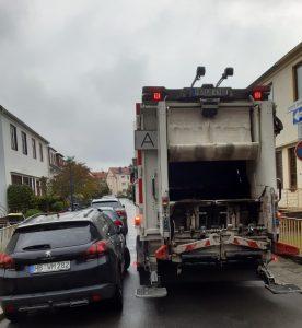 Müllwagen fährt durch enge Wohnstraße an Reihe parkender Autos vorbei.