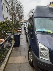 Mit Wohnmobil zugeparkt und mit Mülltonnen zugestellter Gehweg in Wohnstraße mit Vorgärten